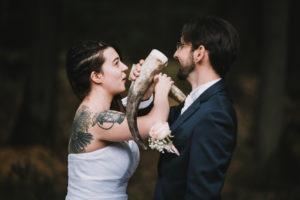Couple de mariés partageant une boisson dans des cornes
