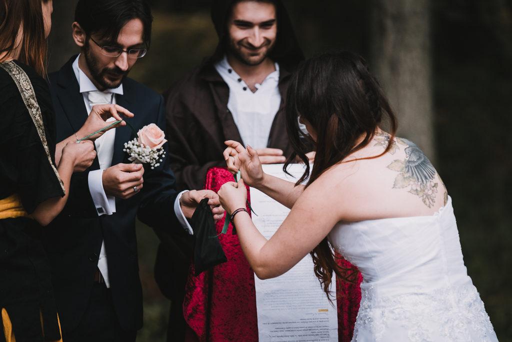 Mariée nouant un ruban autour du poignet de son mari pendant la cérémonie laïque