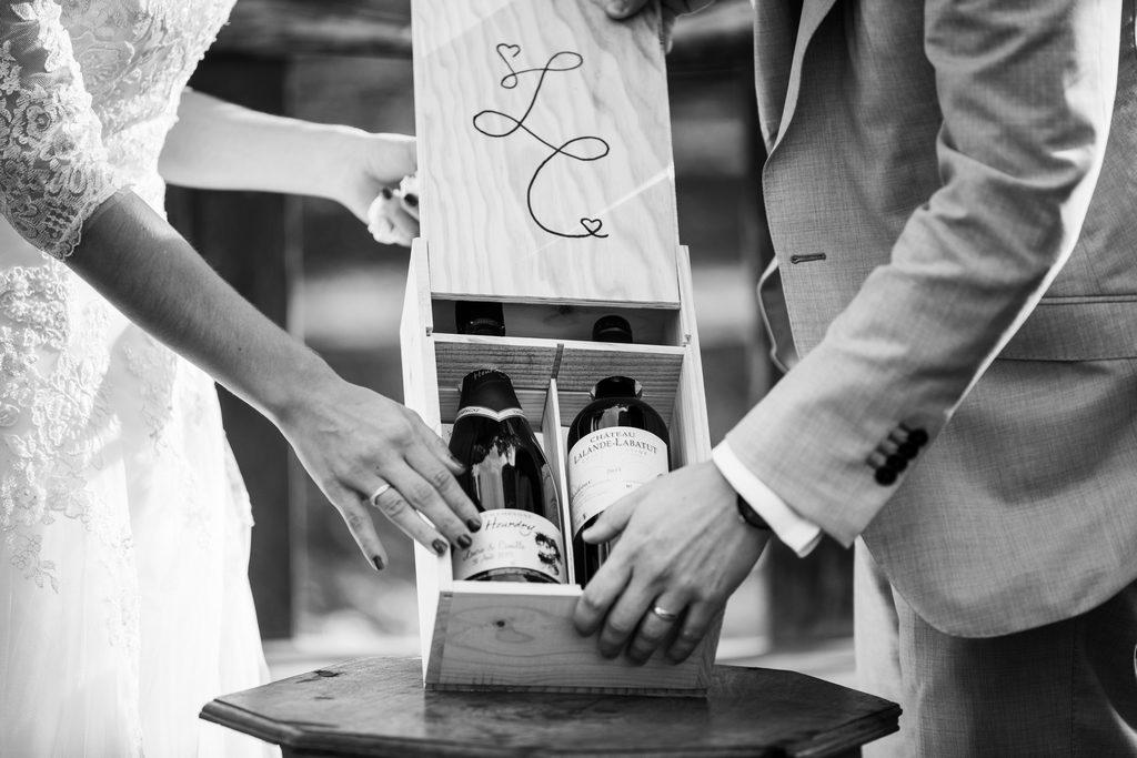 Couple de marié·es refermant une caisse de vin pendant leur cérémonie laïque de mariage en région parisienne