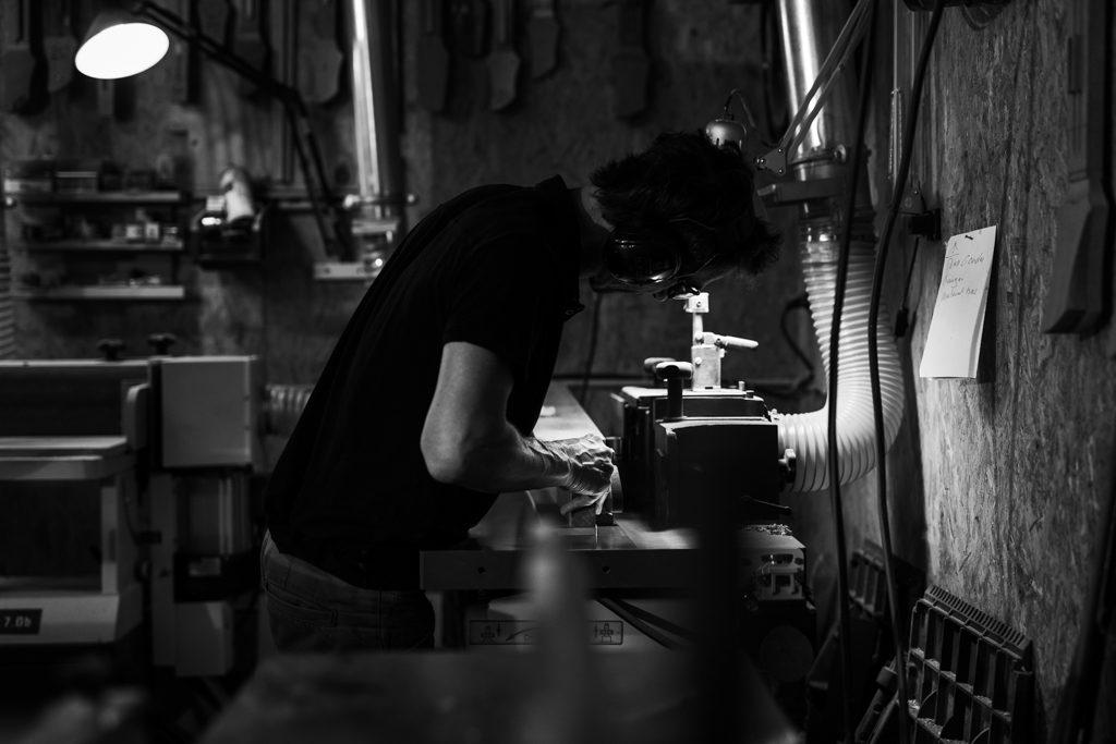 luthier donnant sa forme à un manche de basse