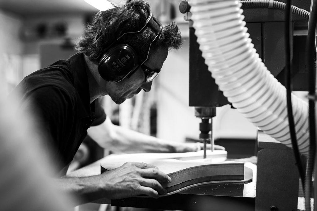 luthier creusant dans le bois pour fabriquer une basse, photo de reportage