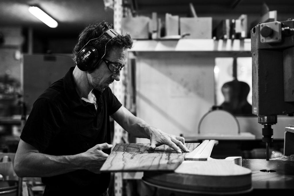 luthier en train de vérifier l'ajustement entre la table et le manche