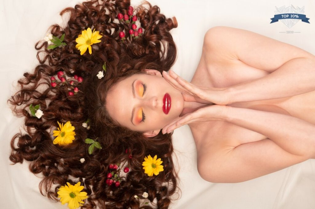 portrait d'une jeune femme rousse avec des fleurs dans les cheveux et un rouge à lèvres rouge