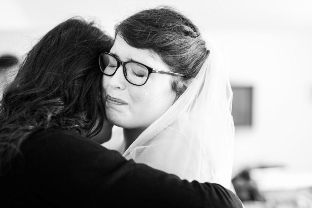 Photo en noir et blanc d'une mariée en larmes pendant les préparatifs du mariage