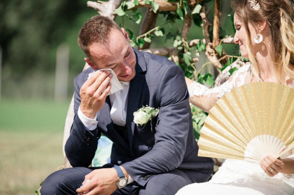 Photo en couleurs d'un marié en pleurs pendant la cérémonie laïque