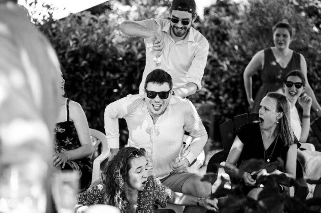 Photo en noir et blanc d'un invité de mariage versant une bouteilel d'eau sur la tête d'un autre invité