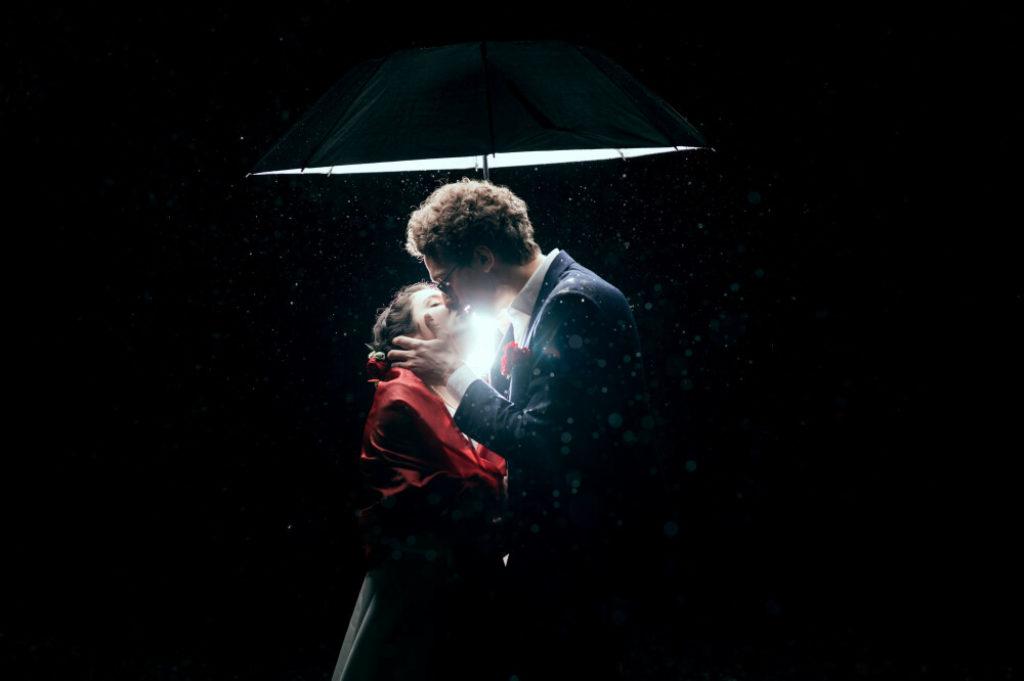 Couple de marié·es s'embrassant sous un parapluie