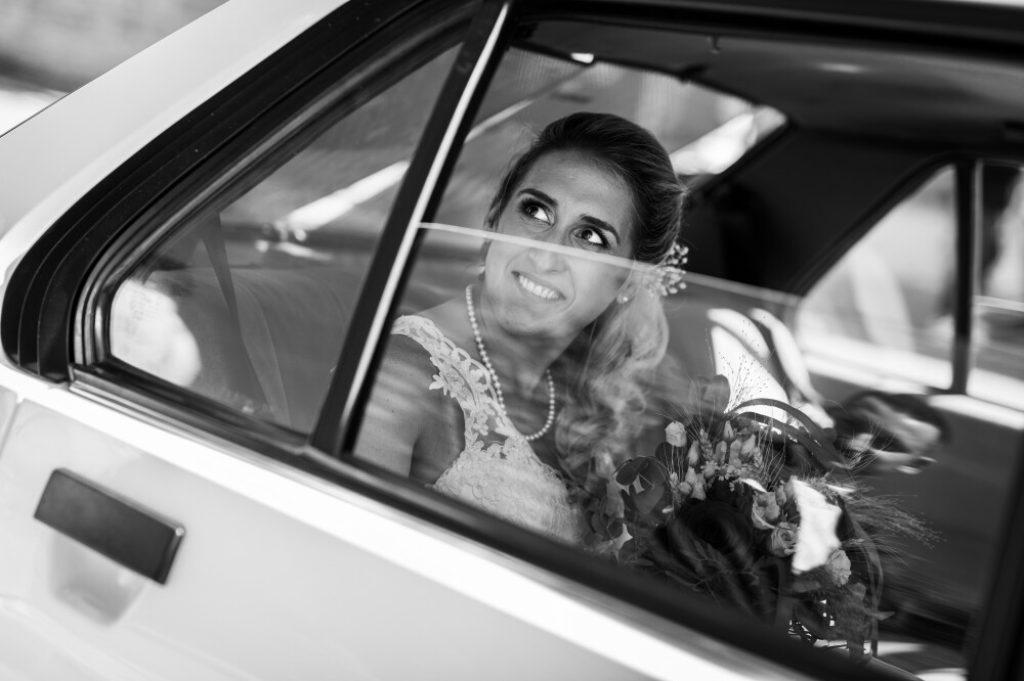 Mariée regardant le marié à travers la vitre de la voiture de mariage. Le marié se reflète dans la vitre de la portière