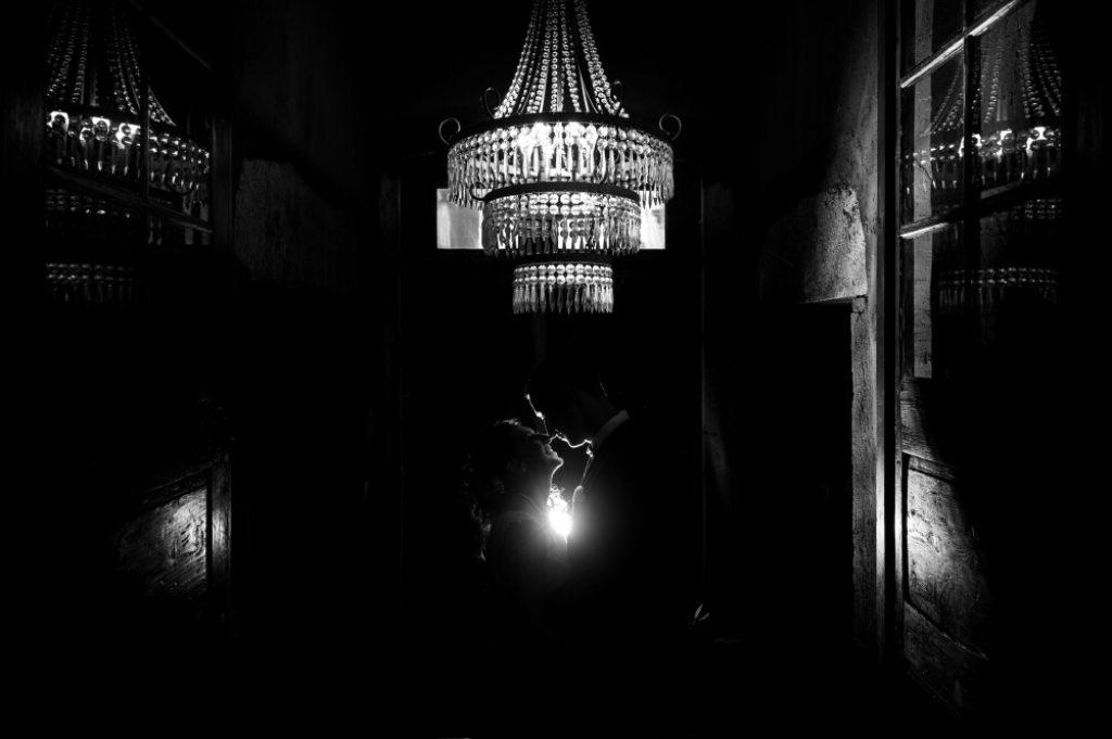 Photo en noir et blanc d'un couple sous un lustre