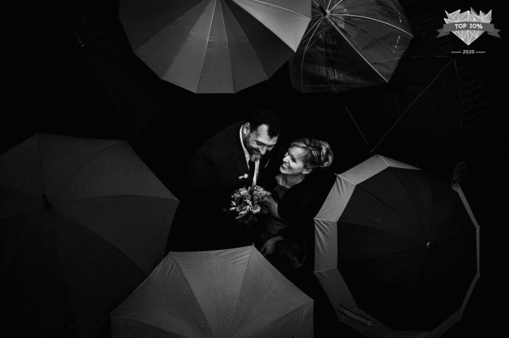 Photo de mariage avec le couple au milieu des parapluies de leurs invité·es