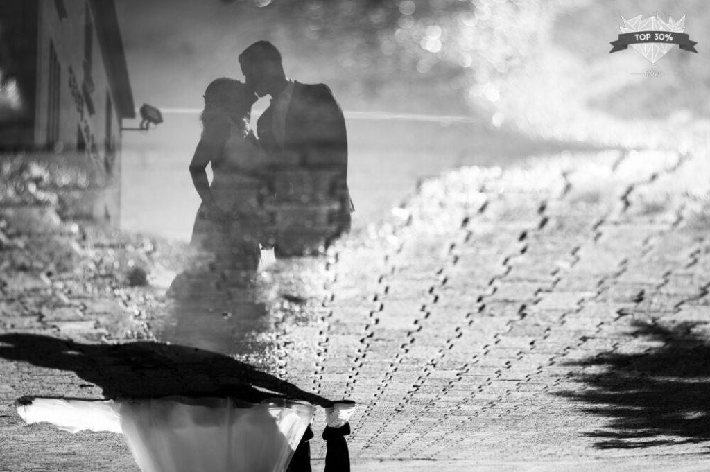 Couple de marié·es se reflétant dans une flaque d'eau