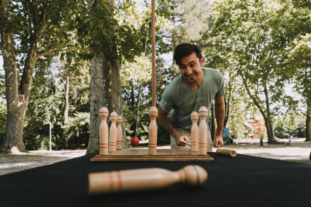 jeune homme jouant au birinic, un jeu géant en bois