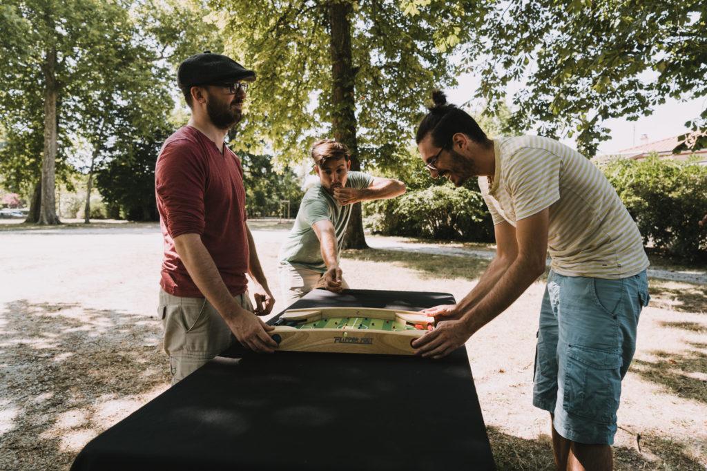 trois personnes jouant au flipper-foot