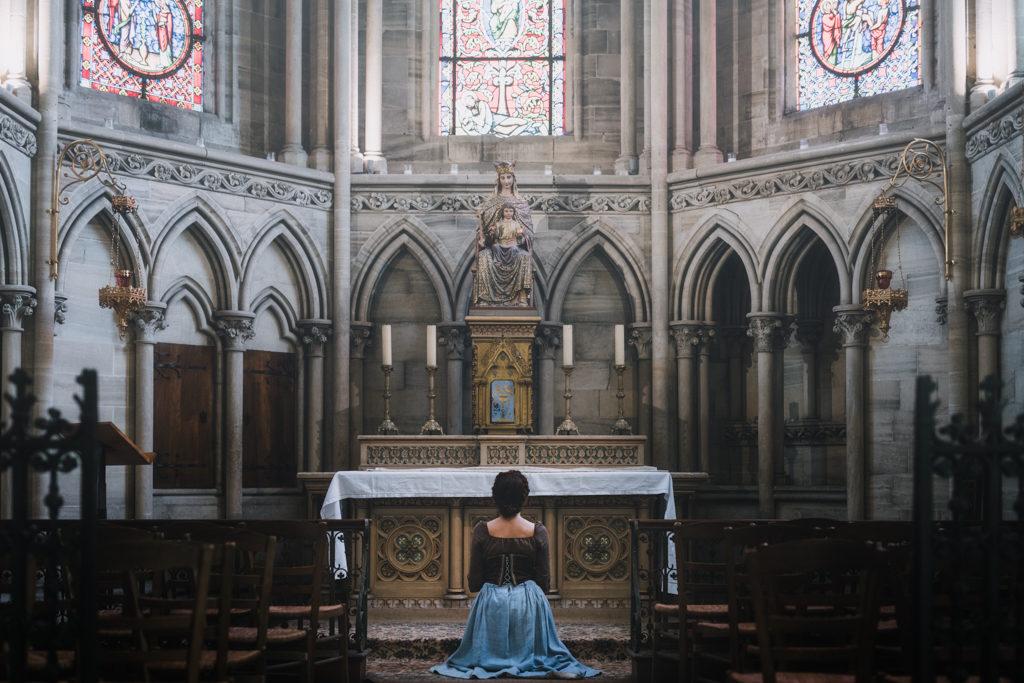 photo d'une jeune femme priant dans la cathédrale de bayeux