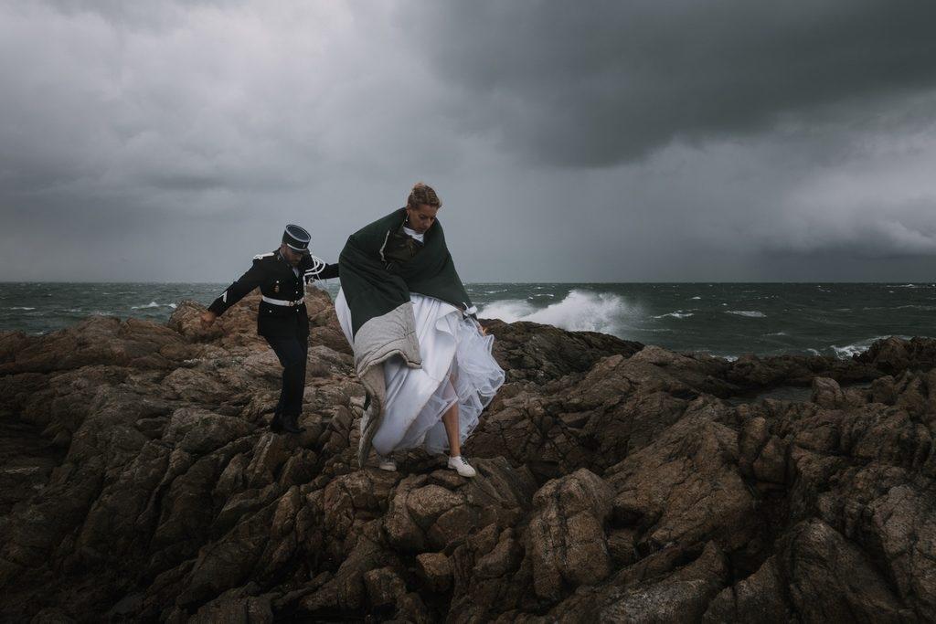 couple de mariés en séance day after, la mariée est recouverte d'un gros duvet pour ne pas prendre froid entre deux photos