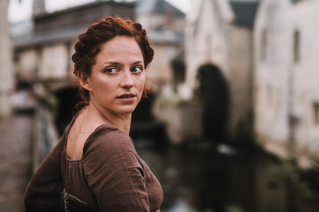 photo d'une jeune femme rousse dans les rues de bayeux cité médiévale