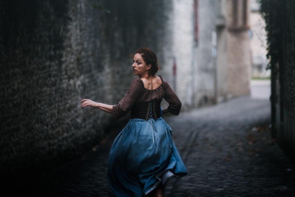 shooting photo en normandie : jeune femme rousse dans une robe d'époque fuyant dans une ruelle