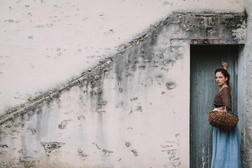 photo dans une rue de bayeux d'une jeune femme en tenue d'époque frappant à une porte