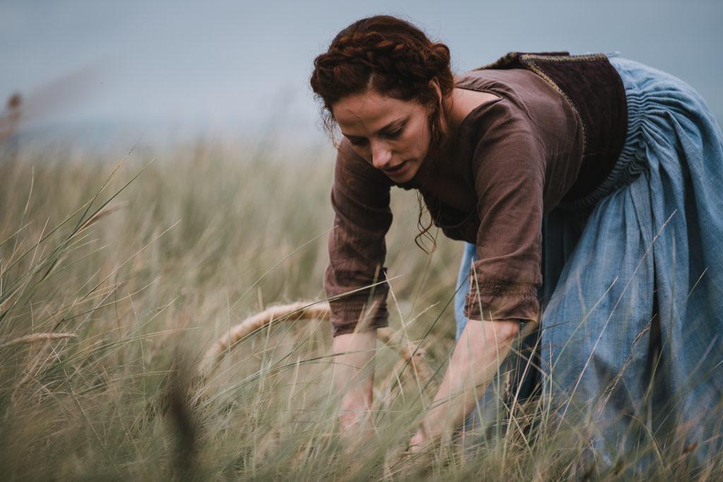 jeune femme vêtue d'une robe bleue et marron, travaillant dans les dunes