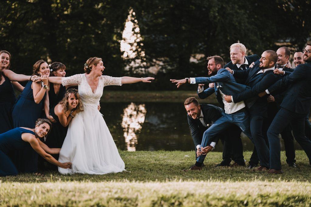 Couple de mariés essayant de se rejoindre, retenus par leurs amis