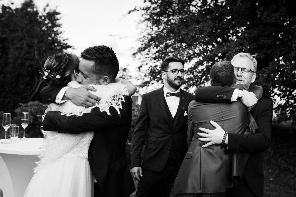 Couple de mariés serrant des invités dans leurs bras