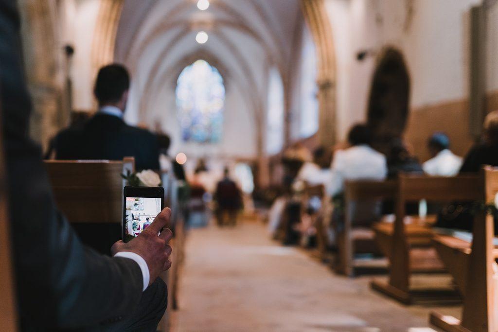 Invité de mariage en train de photographier avec son smartphone pendant l'église