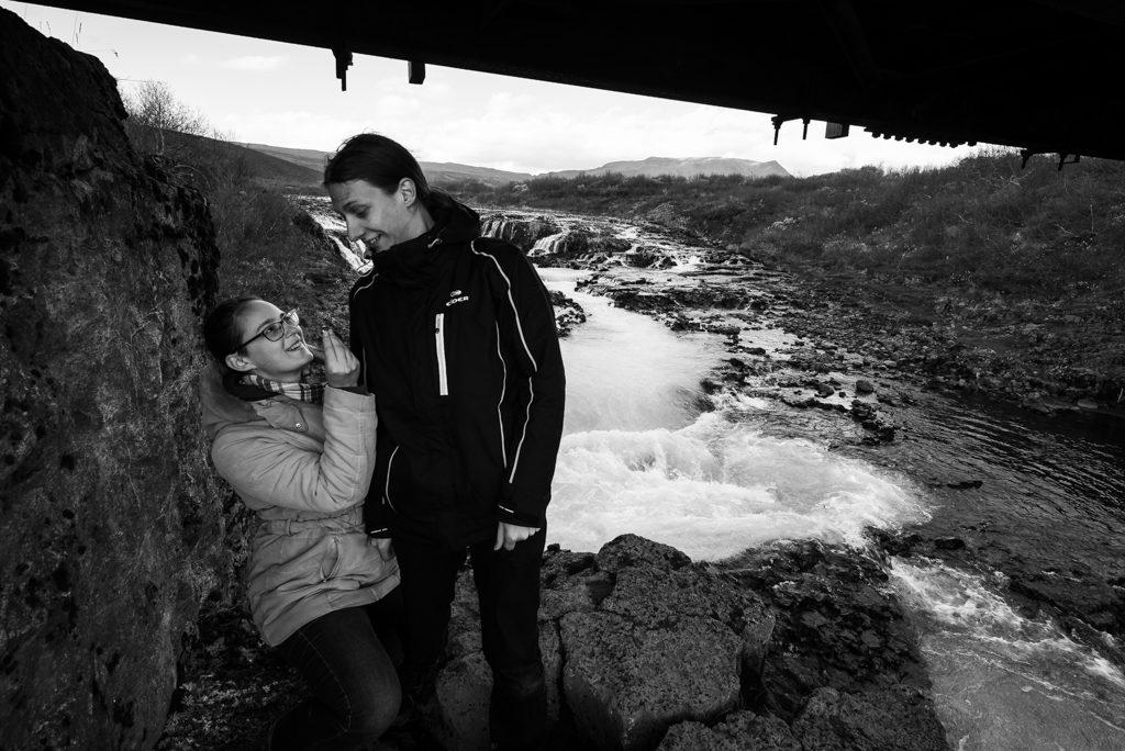 Photo de demande en mariage, une femme est un genou à terre devant un homme, une bague dans la main. A l'arrière plan une chute d'eau