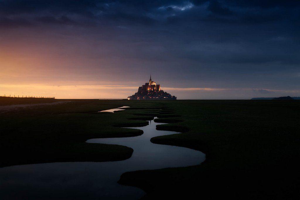 Le mont saint michel au coucher de soleil. Des méandres au premier plan dirigent le regard vers le mont, au centre de l'image à l'arrière-plan