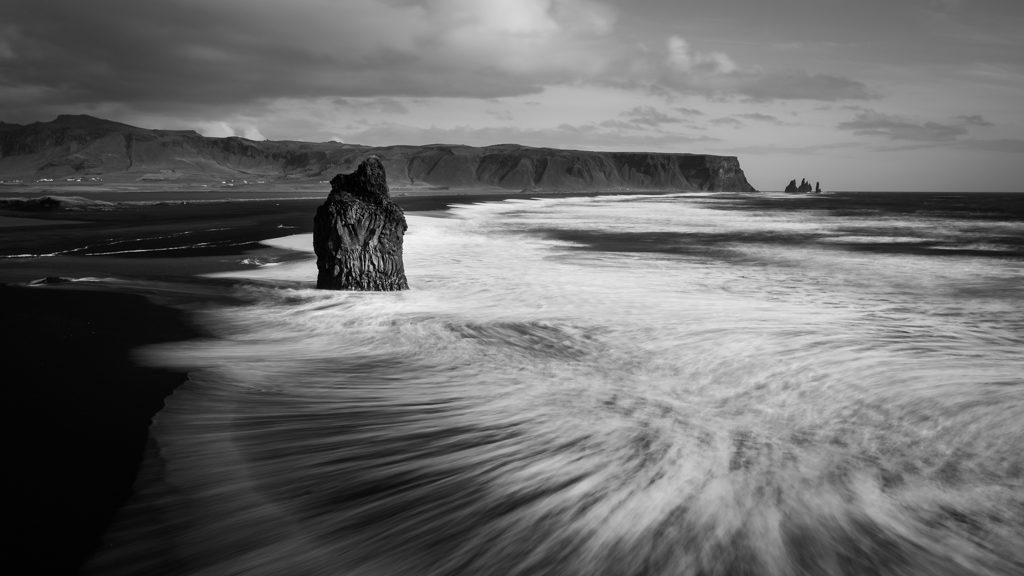 Plage de sable noir en Islande, le mouvement des vagues blanches vient contraster, figé par une pose longue