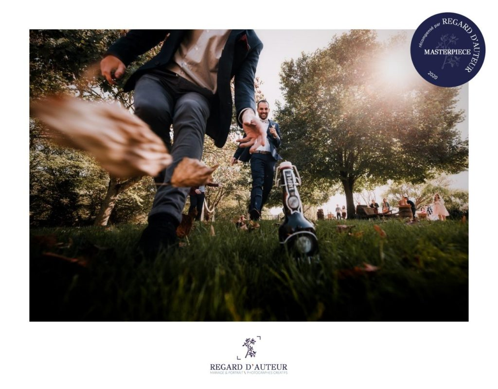 course à la bière pendant un mariage, une bière belge est posée dans l'herbe au premier plan et le marié et ses garçons d'honneur font la course pour l'attraper. Des feuilles mortes volent devant l'objectif