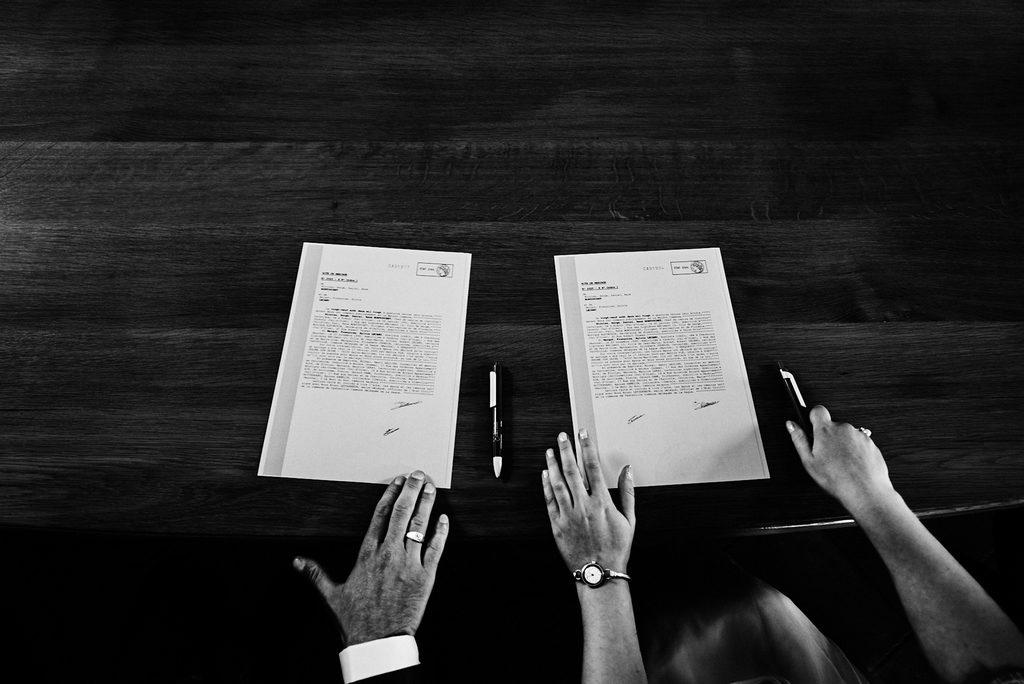 Couple de mariés en train de signer les registres à la mairie vu du dessus