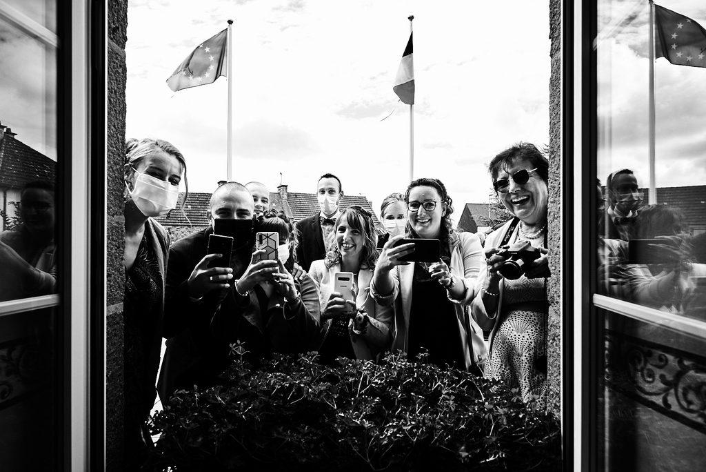 Invités d'un mariage en temps de covid, à l'extérieur, masqués, téléphones brandis vers l'intérieur de la mairie pour prendre des photos