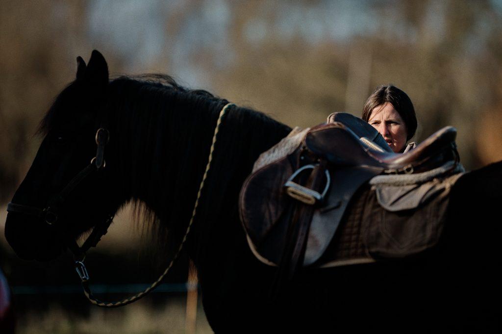 Photo d'une cavalière en train de préparer sa jument avant de partir en balade