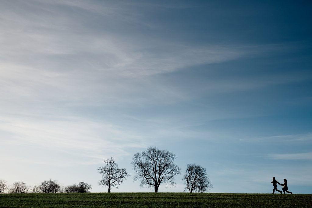 Photo d'un couple courant dans un champ en Normandie