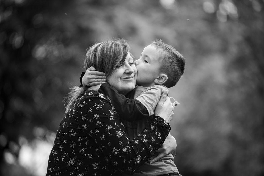 Photo de famille, une mère se fait embrasser par son fils sur la joue