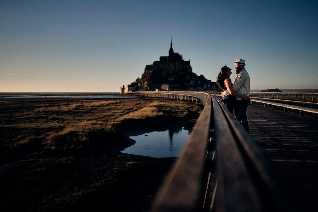Photo d'un couple d'amoureux devant le mont saint-michel en Normandie