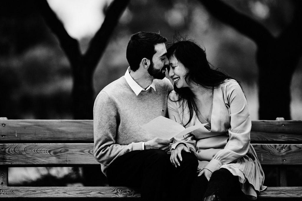 Couple assis sur un banc, l'un contre l'autre. L'une des deux personnes tient une feuille de papier.