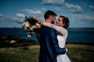 Couple de mariés avec la mer en arrière-plan