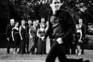 Photo de groupe avec quelqu'un qui passe en courant devant l'objectif