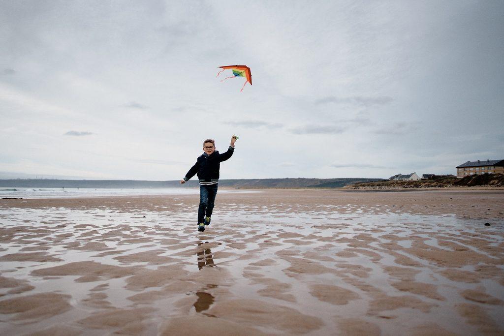 Photo d'un enfant sur une plage tirant un cerf-volant