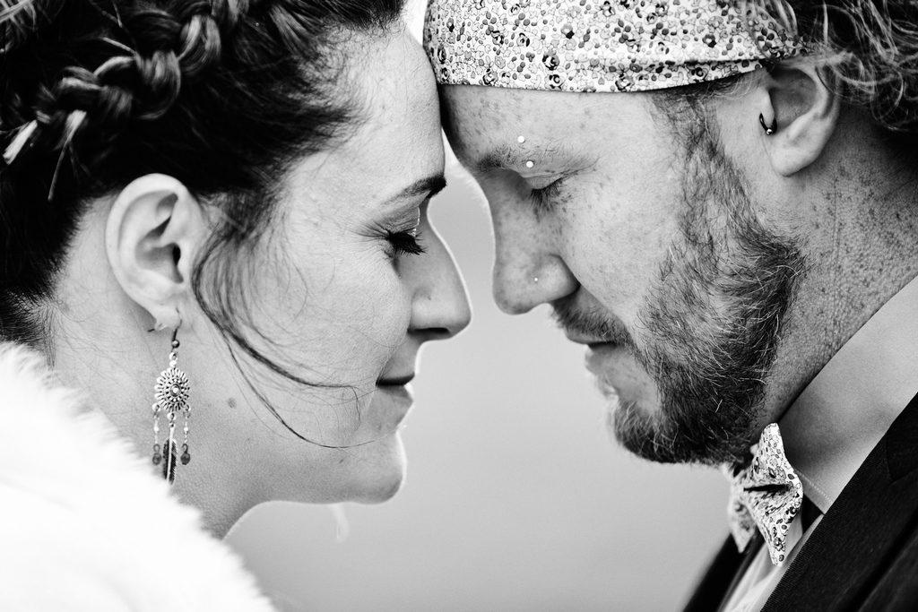 Photo de couple pendant un mariage, front contre front, les mariés semblent partager un amour solide