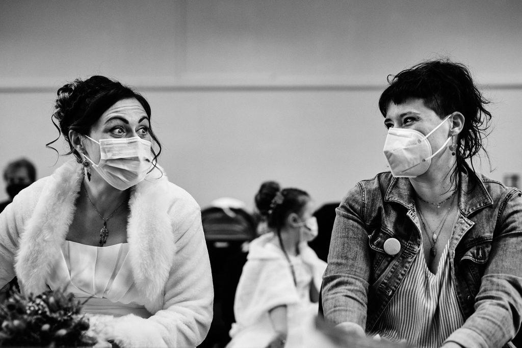 Mariée et sa témoin échangeant un regard complice pendant la cérémonie civile à la mairie, les deux personnes portent un masque car la cérémonie était pendant le covid