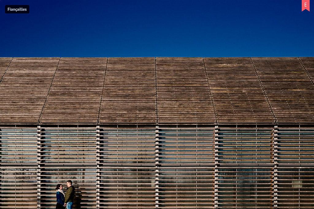 Photo d'un couple face-à-face, devant un bâtiment marron, avec le ciel bleu au-dessus