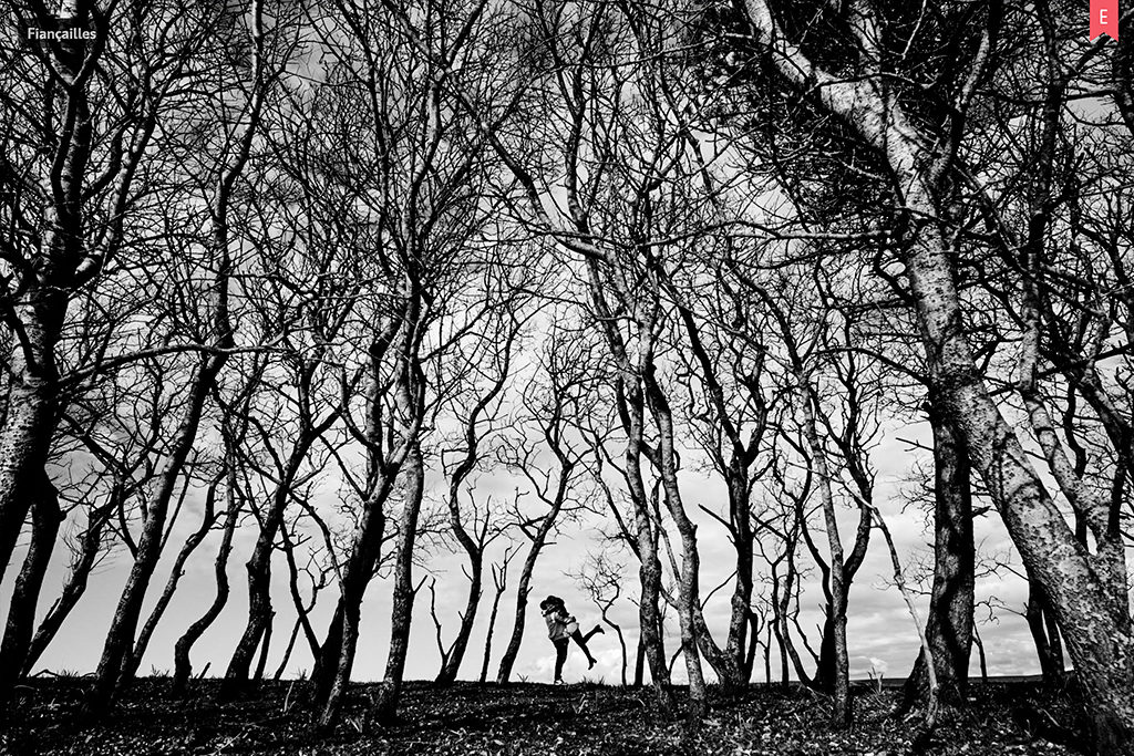 Photo de couple avec une femme sautant dans les bras d'un homme, la jambe levée, entre des arbres qui forment un puzzle