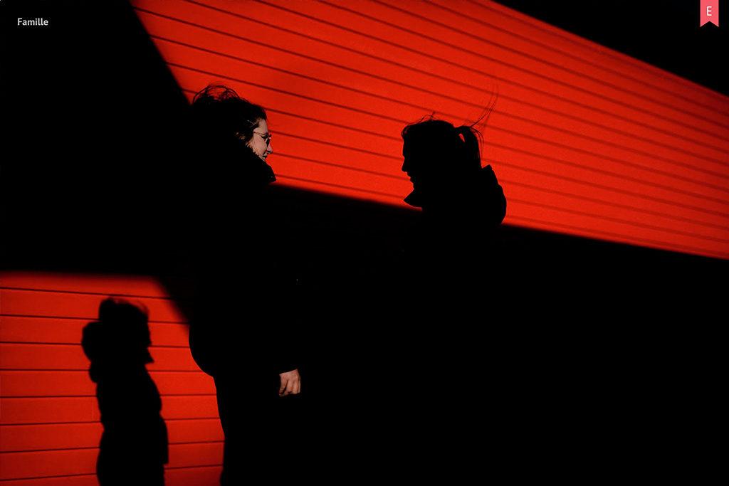 Photo de famille avec un jeu de silhouette et de contrastes d'ombres avec pour fond un mur rouge