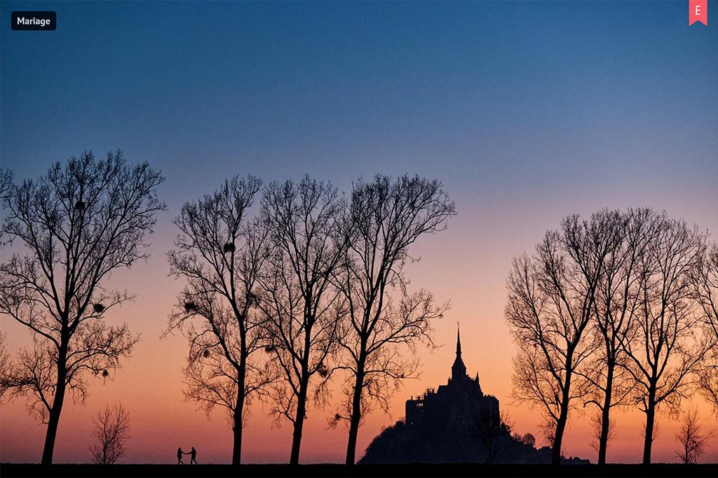 Photo du mont saint michel avec un couple avancant main dans la main entre les arbres, récompensée sur mywed par un choix éditeur