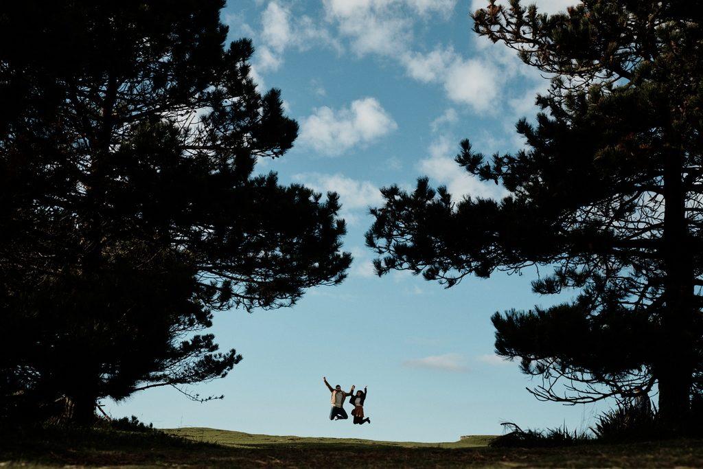 Couple sautant en l'air entre deux arbres