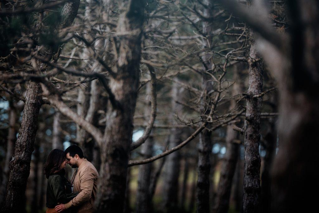 Couple se tenant front contre front dans une forêt
