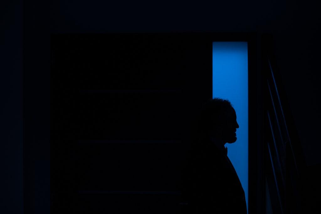 Photo brute telle qu'elle a été prise : la silhouette d'un homme se détache sur une bande bleue