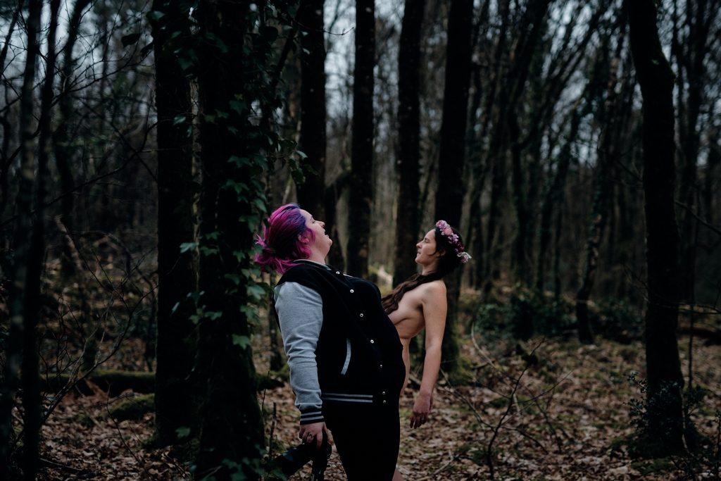 Photographe pendant une séance de nu en forêt, montrant au modèle la position à adopter